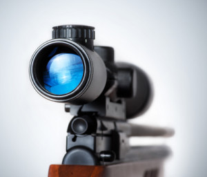 Weapon gun target concept. Closeup of a sniper rifle telescope glass lens isolated